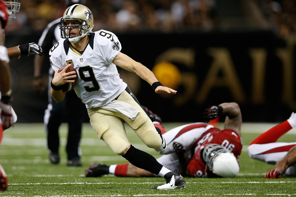 Description of . Drew Brees #9 of the New Orleans Saints runs with the ball against the Arizona Cardinals at the Mercedes-Benz Superdome on September 22, 2013 in New Orleans, Louisiana.  (Photo by Chris Graythen/Getty Images)