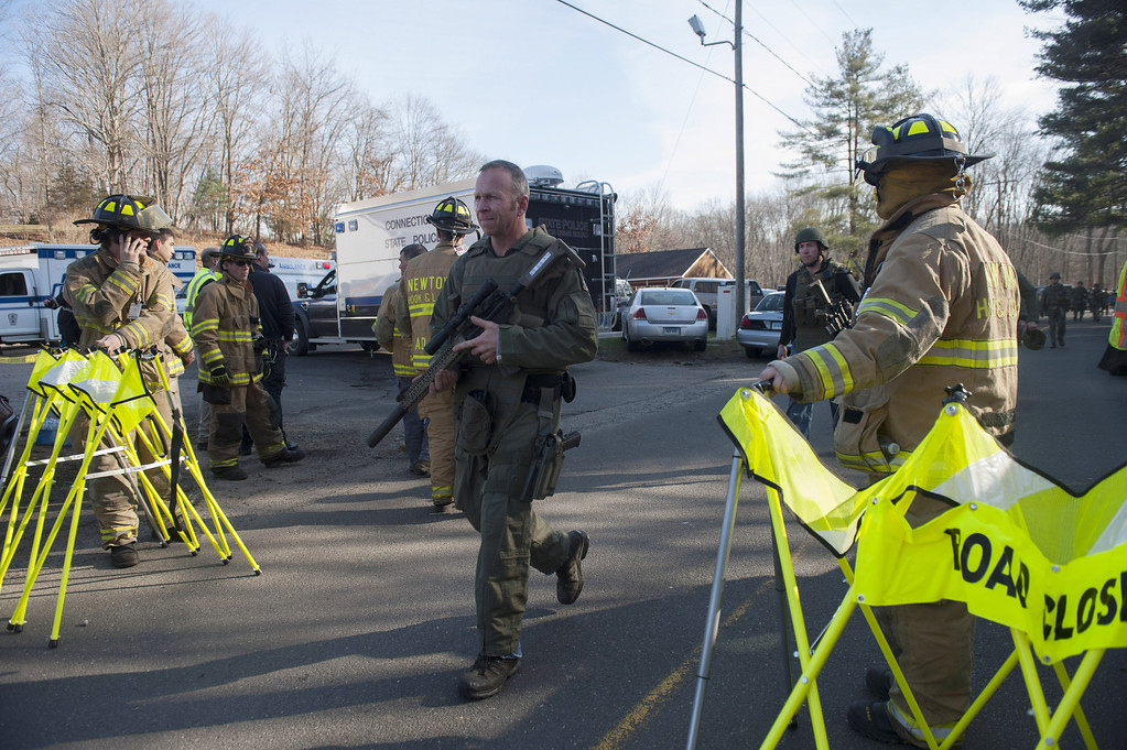 Description of . Connecticut State Police walk near the scene of an elementary school shooting on December 14, 2012 in Newtown, Connecticut. According to reports, there are more than 20 dead, most children, after a gunman opened fire in at the Sandy Hook Elementary School. The shooter was also killed.  (Photo by Douglas Healey/Getty Images)
