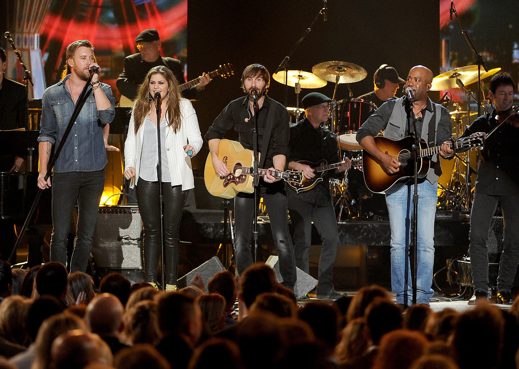 Description of . Charles Kelley, and from left, Hillary Scott and Dave Haywood, of the musical group Lady Antebellum, and Darius Rucker perform on stage at the 49th annual Academy of Country Music Awards at the MGM Grand Garden Arena on Sunday, April 6, 2014, in Las Vegas. (Photo by Chris Pizzello/Invision/AP)