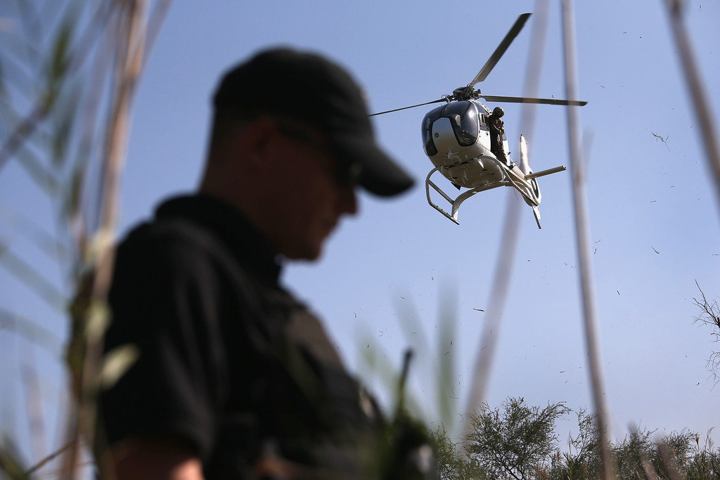 Description of . MISSION, TX - APRIL 11:  U.S. Office of Air and Marine (OAM), agent Jake Dreher stands over a drug smuggler on the bank of the Rio Grande River at the U.S.-Mexico Border on April 11, 2013 in Mission, Texas. Agents with helicopter support from the U.S. Office of Air and Marine broke up a marijuana smuggling operation from Mexico into Texas. In addition to the drug smuggling, U.S. Border Patrol agents say they have also seen an additional surge in immigrant traffic in Texas\' Rio Grande Valley sector since immigration reform negotiations began this year in Washington D.C.  (Photo by John Moore/Getty Images)