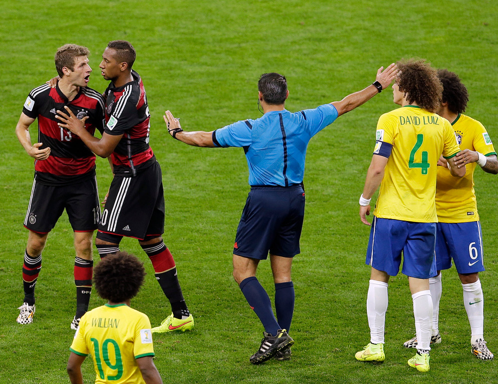 Description of . Referee Marco Rodriguez from Mexico mediates between Germany's Thomas Mueller, left, and Brazil's David Luiz (4) during the World Cup semifinal soccer match between Brazil and Germany at the Mineirao Stadium in Belo Horizonte, Brazil, Tuesday, July 8, 2014. (AP Photo/Hassan Ammar)