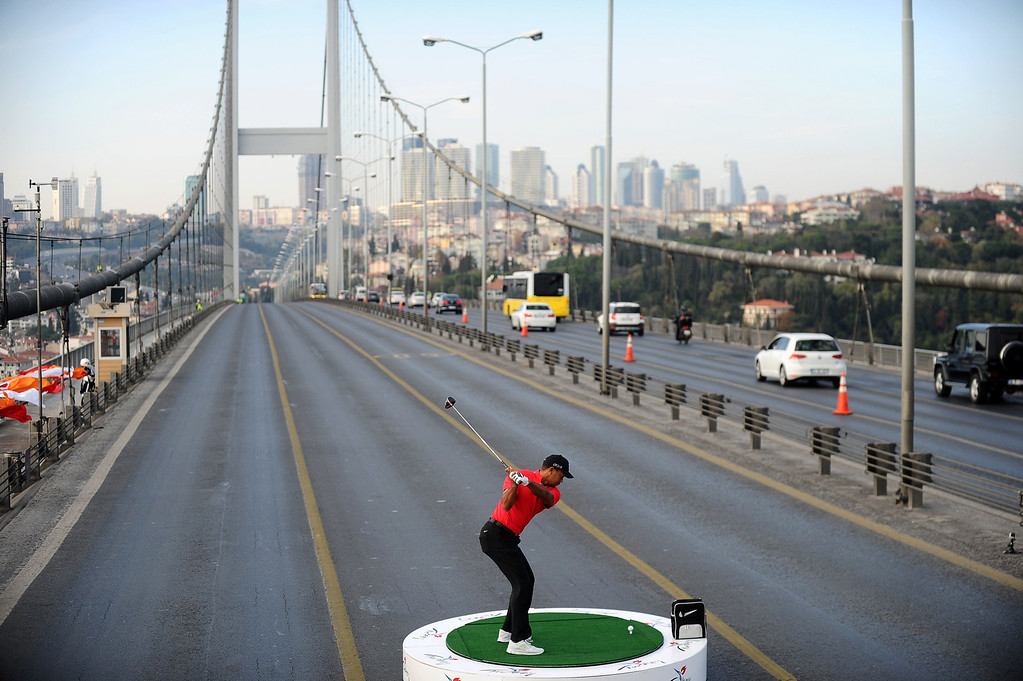 Description of . U.S. golfer Tiger Woods hits a ball as he poses during an event to promote the upcoming Turkish Airlines Open golf tournament, on the Bosphorus Bridge that links the city's European and Asian sides, in Istanbul, on November 5, 2013. Woods was in Turkey to attend the tournament, which took place between November 7 to 10.  BULENT KILIC/AFP/Getty Images