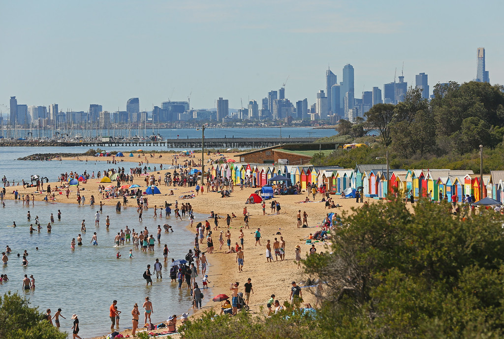 Description of . MELBOURNE, AUSTRALIA - DECEMBER 25:  People enjoy a day at the beach on Christmas Day at Brighton Beach on December 25, 2013 in Melbourne, Australia.  Brighton Beach features 82 colourful bathing boxes, which are one of the tourist icons of Melbourne. Temperatures in Melbourne on Christmas Day topped thirty degrees celcius.  (Photo by Scott Barbour/Getty Images)