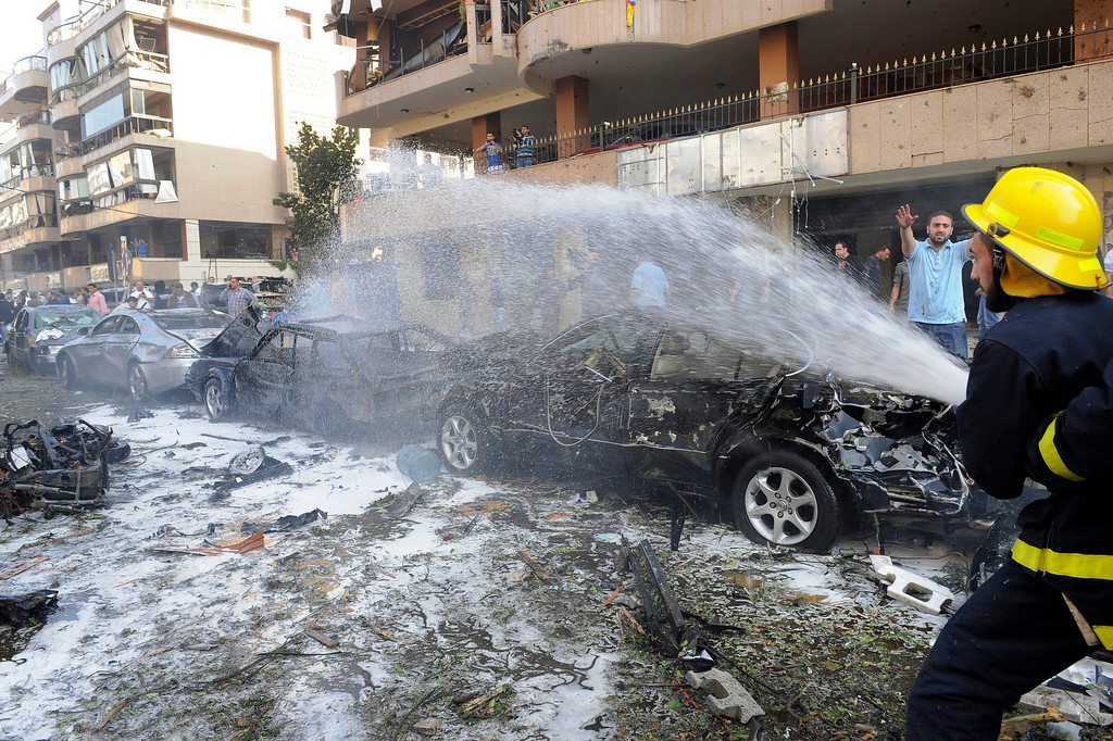 Description of . Lebanese firefighters hose down smoldering vehicles at the site of  explosions close to the Iranian embassy in south Beirut, Lebanon, 19 November 2013. Two explosion rocked southern Beirut on 19 November near the Iranian embassy, killing at least 17 and injuring 60 others according to latest reports.  EPA/WAEL HAMZEH