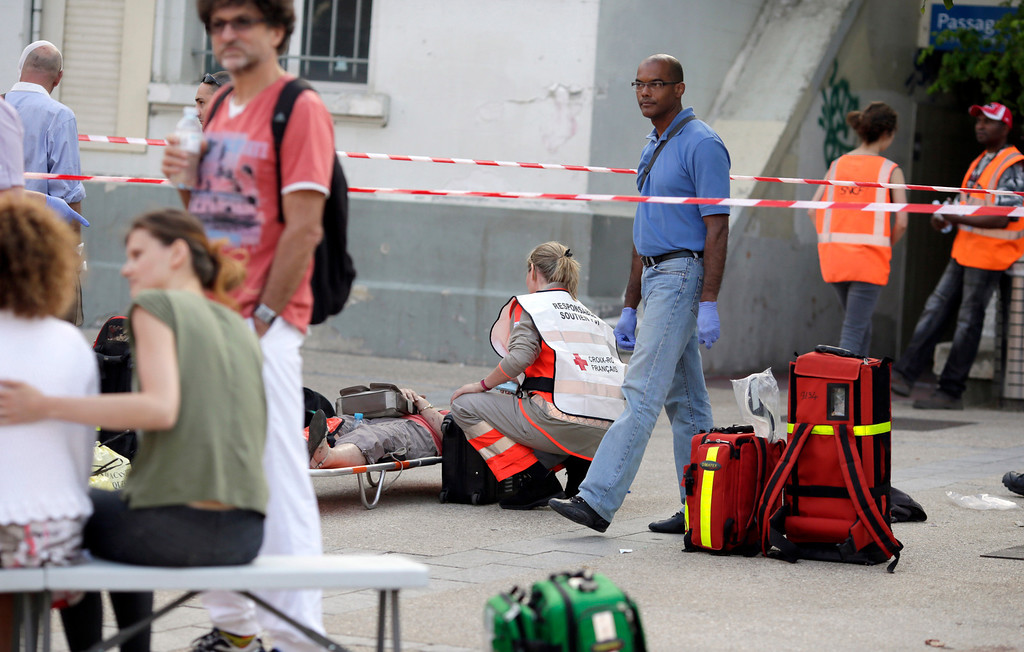 Description of . A Red Cross worker attends to a person on a stretcher at the site of a train accident in the railway station of Bretigny-sur-Orge, Friday, July 12, 2013 near Paris. (AP Photo/Kenzo Tribouillard, Pool)