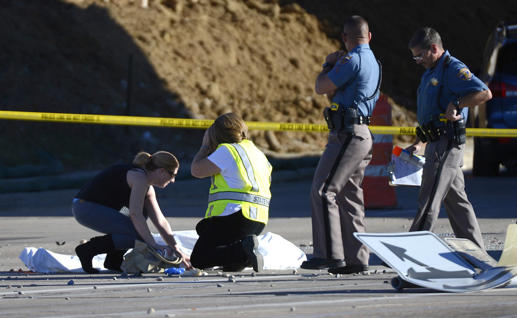 Description of . Family is escorted to a victim at the fatal crash at Broadwway at the C-470 exit in the northbound lane of Broadway.  John Leyba, The Denver Post