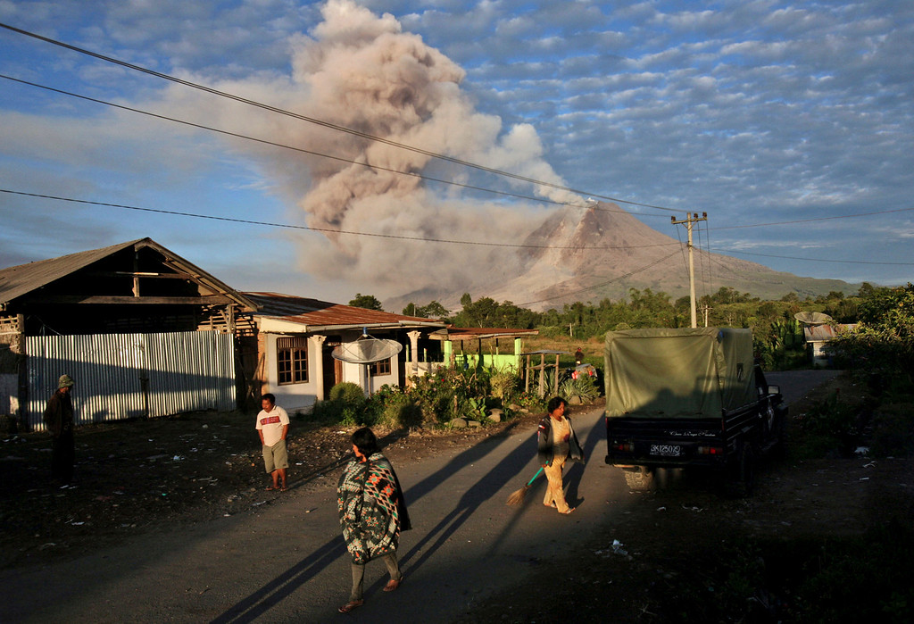 Description of . Villagers start their morning routine as Mount Sinabung releases volcanic materials into the air in Perteguhan, North Sumatra, Indonesia, Monday, Jan. 6, 2014. The 2,600-meter (8,530-foot) volcano has sporadically erupted since September. Authorities extended a danger zone around a rumbling volcano in western Indonesia on Sunday after it spewed blistering gas farther than expected, sending panicked residents streaming down the sides of the mountain. (AP Photo/Binsar Bakkara)