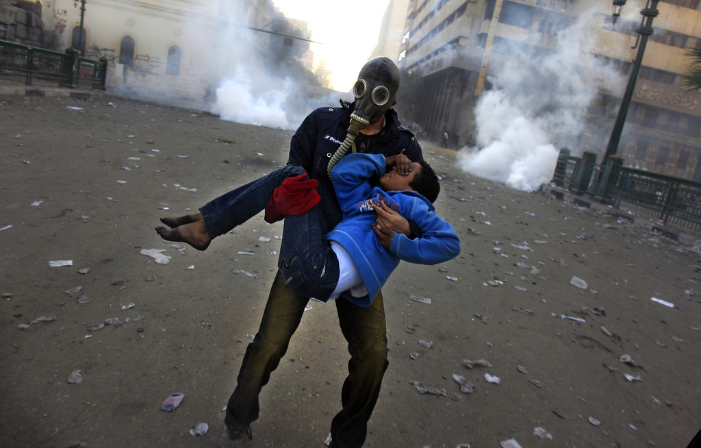 . An Egyptian protester evacuates an injured boy during clashes near Tahrir Square, Cairo, Egypt, Friday, Jan. 25, 2013. Two years after Egypt\'s revolution began, the country\'s schism was on display Friday as the mainly liberal and secular opposition held rallies saying the goals of the pro-democracy uprising have not been met and denouncing Islamist President Mohammed Morsi. (AP Photo/Khalil Hamra)