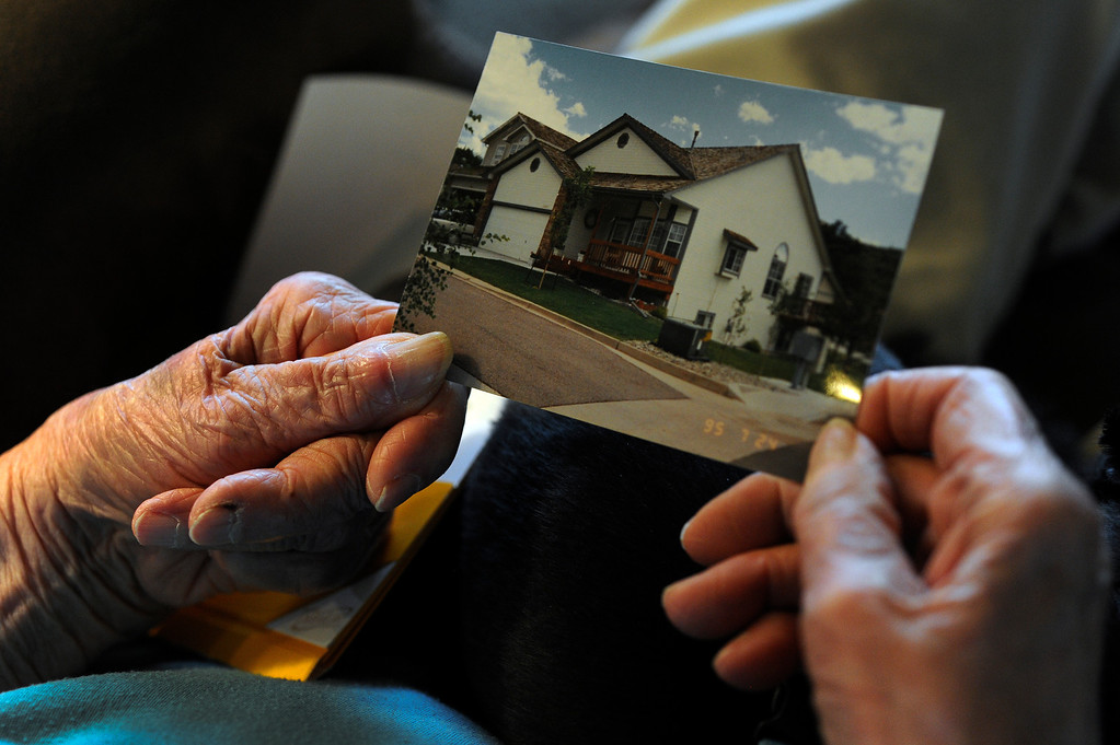 Description of . Lauretta Anzalone looks at pictures of her Mountain Shadows home that was destroyed in  the Waldo Canyon fire in Colorado Springs, CO, Saturday June 30, 2012. She is currently staying with her niece Jayne Lee, right, and her husband David, in Colorado Springs. Anzalone said,