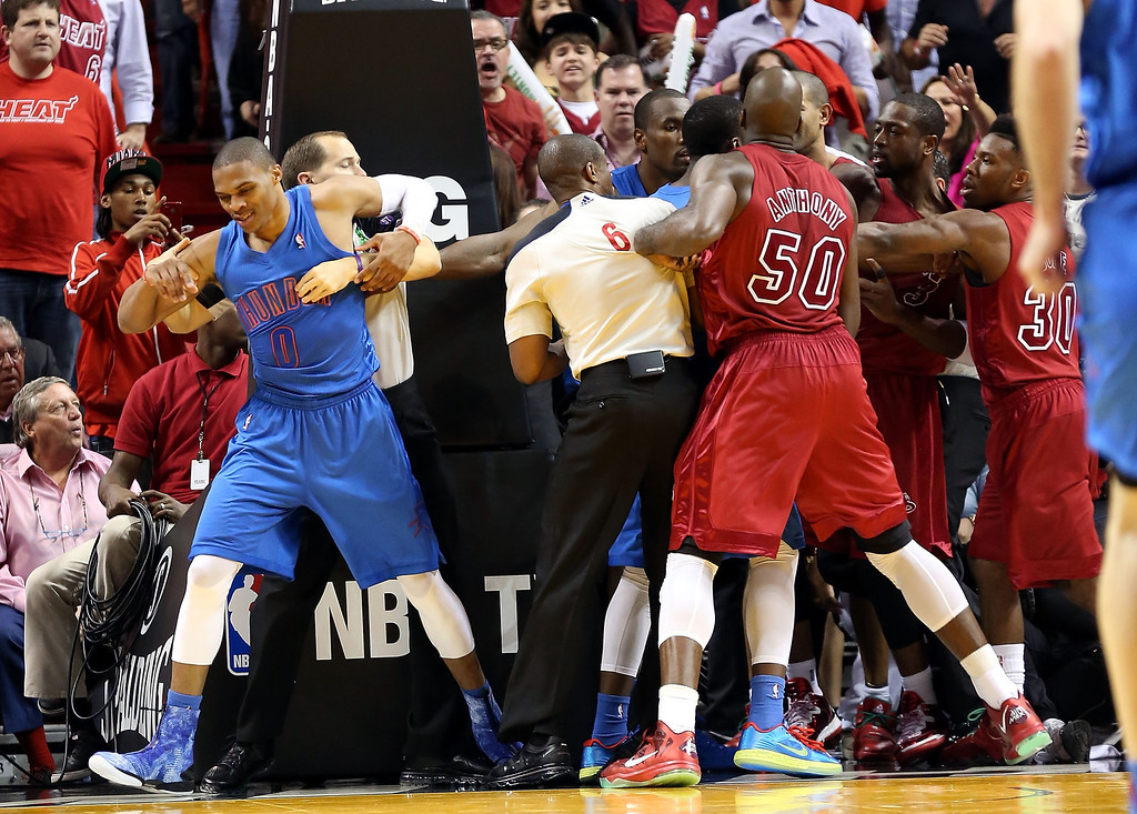 Description of . MIAMI, FL - DECEMBER 25: Guard Russell Westbrook #0 of the Oklahoma City Thunder is held by the referee during a scuffle with the Miami Heat at AmericanAirlines Arena on December 25, 2012 in Miami, Florida. The Heat defeated the Thunder 103-97.  (Photo by Marc Serota/Getty Images)