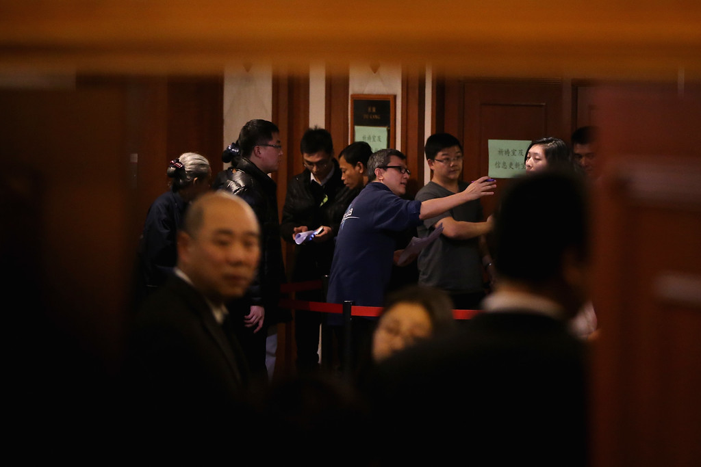 Description of . Malaysia Airlines staff arrange organise relatives of passengers onboard Malaysia Airlines flight MH370 as they line up to receive a special condolence payment of 31,000 CNY (almost 5,000 USD) at Lido Hotel on March 12, 2014 in Beijing, China.  (Photo by Feng Li/Getty Images)