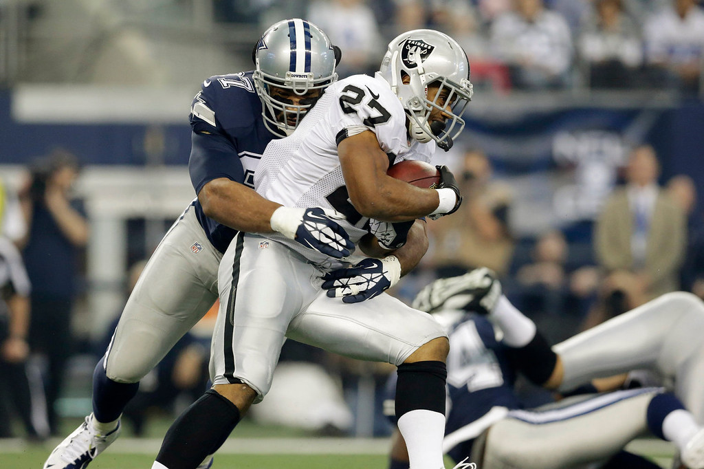 Description of . Oakland Raiders running back Rashad Jennings (27) is tackled by Dallas Cowboys defensive tackle Jason Hatcher (97) during the first half of an NFL football game, Thursday, Nov. 28, 2013, in Arlington, Texas.  (AP Photo/LM Otero)
