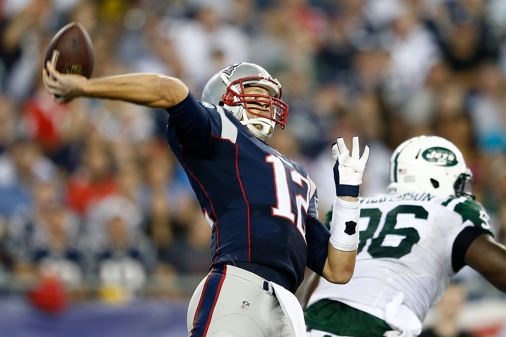 Description of . Quarterback Tom Brady #12 of the New England Patriots throws the ball in the first half while taking on the New York Jets at Gillette Stadium on September 12, 2013 in Foxboro, Massachusetts.  (Photo by Jim Rogash/Getty Images)