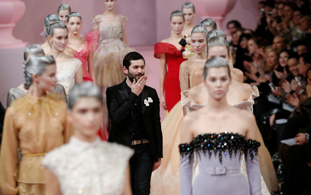 Description of . French fashion designer Alexis Mabille, centre, blows a kiss as he receives acknowledgement for his Spring Summer 2013 Haute Couture fashion collection, presented in Paris, Monday, Jan. 21, 2013. (AP Photo/Christophe Ena)