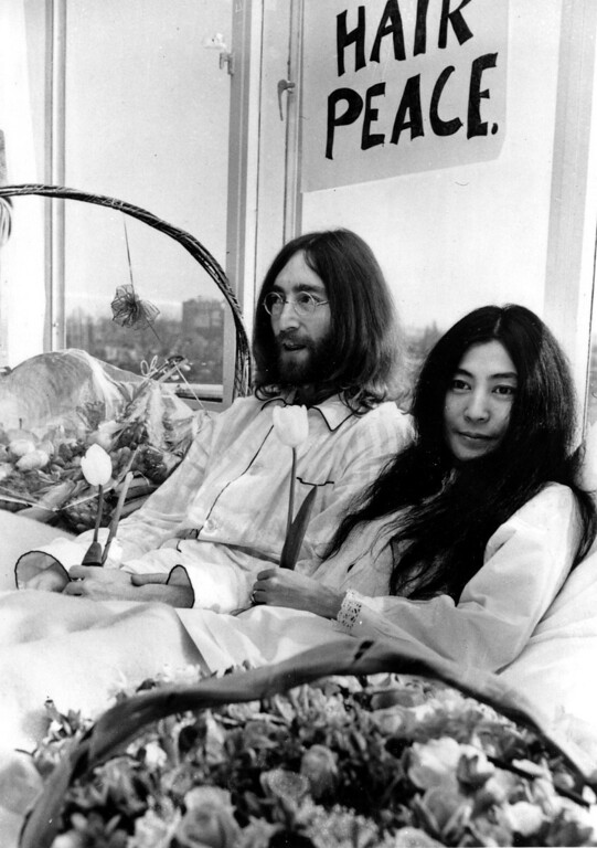 Description of . Beatle John Lennon and his wife, Yoko Ono, hold a bed-in for peace in room 902, the presidential suite at the Hilton Hotel in Amsterdam on March 25, 1969.  The newlyweds, holding solitary tulips, begin a seven-day Love-In to protest the Vietnam War.  (AP Photo)