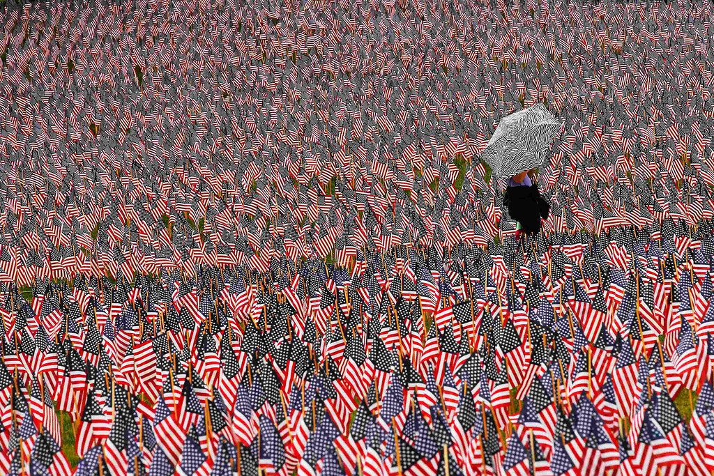 Description of . A pedestrian carrying an umbrella walks through a Memorial Day display of United States flags on the Boston Common in Boston, Massachusetts May 23, 2013.  According to the Massachusetts Military Heroes Fund, the flags are planted on the Common for fallen Massachusetts service members at the Memorial Day holiday, which will be celebrated May 27 in the U.S.   REUTERS/Brian Snyder
