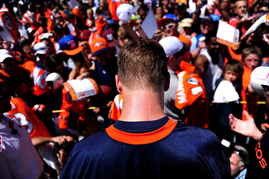 Description of . Denver Broncos quarterback Peyton Manning (18) signs autographs during the first day of Broncos training camp at Dove Valley on Thursday, July 26, 2012. AAron Ontiveroz, The Denver Post
