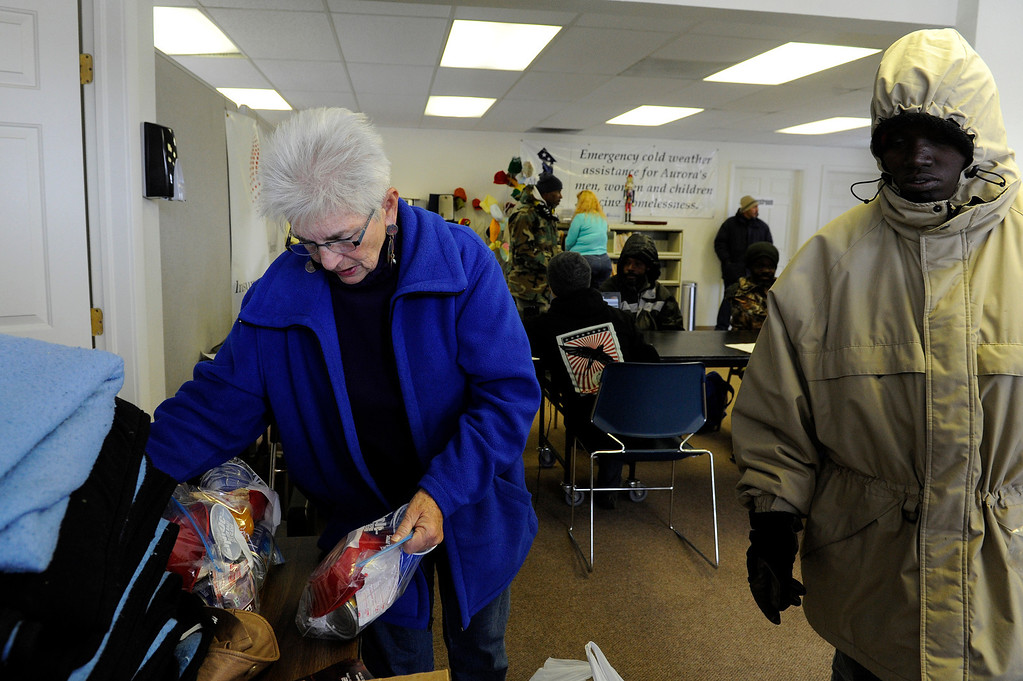 Description of . AURORA, CO - NOVEMBER 21: Judy Byer, left,  hands out food kits to homeless clients during an Aurora Warms the Night Cold Weather Shelter Program on November 21, 2013, in Aurora, Colorado. AWTN provides assistance to the homeless with a number of initiatives, including the Cold Weather Shelter Program which gives clients motel vouchers, food, clothing and hygiene kits on nights expected to be 20 degrees or colder. (Photo by Anya Semenoff/YourHub)