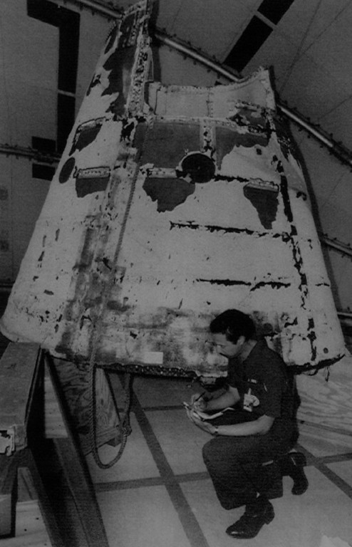Description of . National Transportation Safety Board investigator John White kneels in front of the nose cone of the Challenger's right solid rocket booster. The right solid rocket booster is suspected by investigators of contributing to the explosion of Challenger on January 28th, 1986.  Denver Post Library Archive