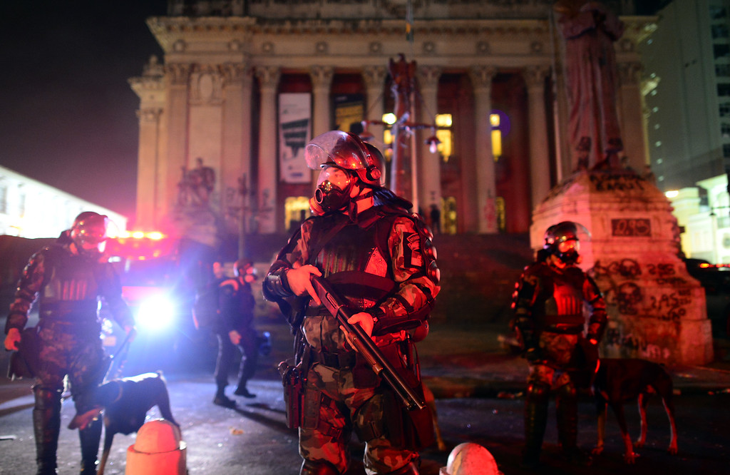 Description of . Riot police officers stand guard outside the Municipal Theatre during clashes in Rio de Janeiro's downtown, on June 17, 2013. Youths clashed with police in central Rio Monday as more than 200,000 people marched in major Brazilian cities to protest the billions of dollars spent on the Confederations Cup and higher public transport costs.  CHRISTOPHE SIMON/AFP/Getty Images