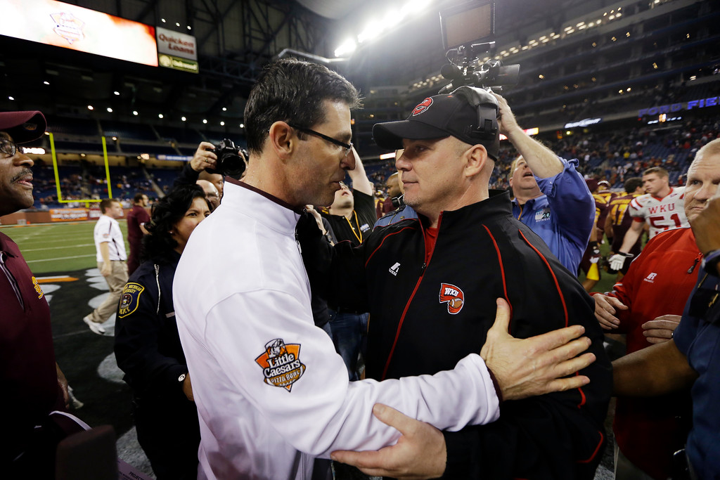 Description of . Western Kentucky interim head coach Lance Guidry, right, congratulates Central Michigan head coach Dan Enos, left, after their Little Caesars Pizza Bowl NCAA college football game at Ford Field in Detroit, Wednesday, Dec. 26, 2012. Central Michigan won 24-21. (AP Photo/Carlos Osorio)