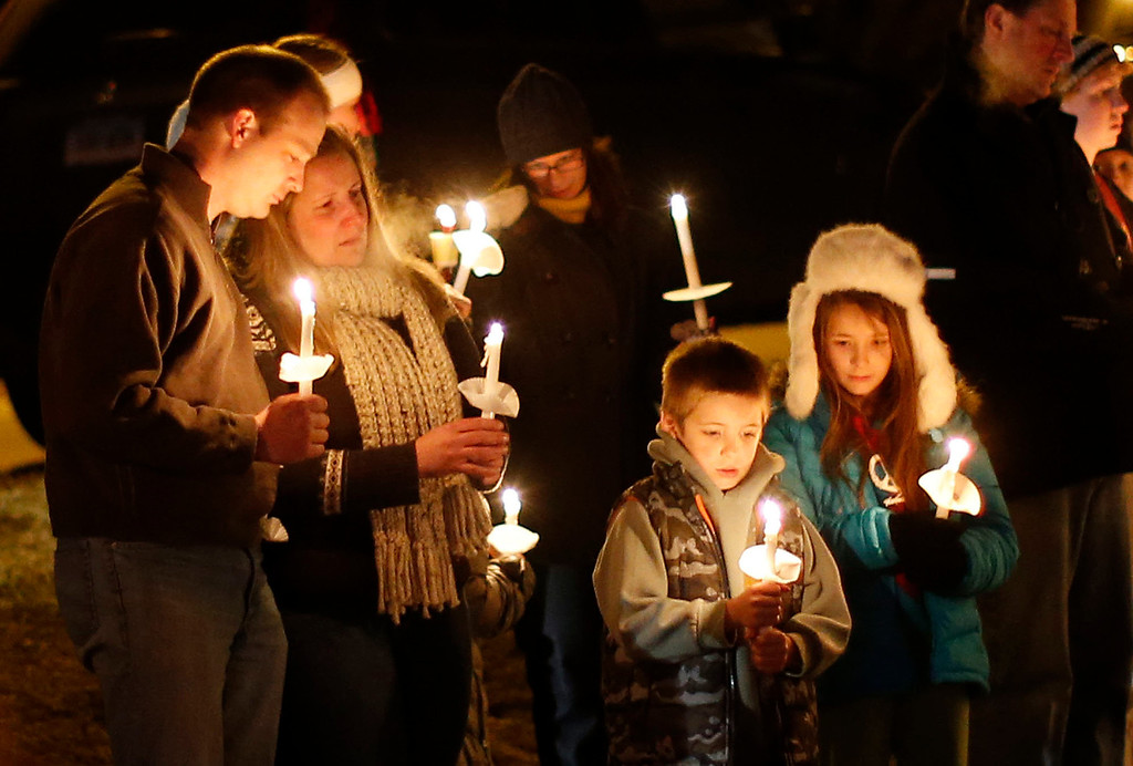 Description of . Mourners gather for a candlelight vigil at Ram's Pasture to remember shooting victims, Saturday, Dec. 15, 2012 in Newtown, Conn.  A gunman walked into Sandy Hook Elementary School in Newtown Friday and opened fire, killing 26 people, including 20 children. (AP Photo/Jason DeCrow)
