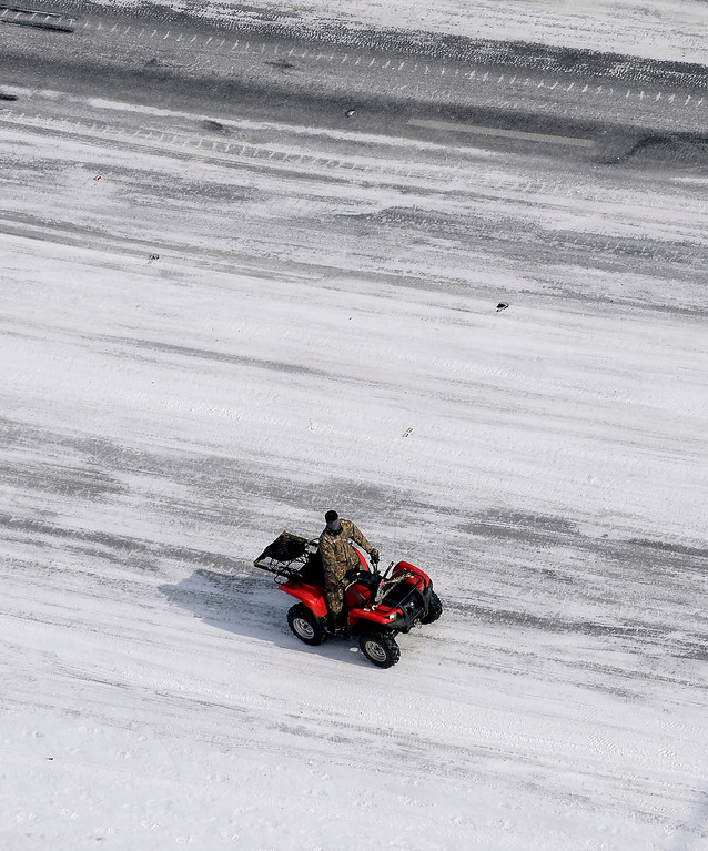 Description of . In this aerial view, A good Samaritan on a four-wheeler patrols I-75 south at West Paces Ferry Rd. after a winter snow storm Wednesday, Jan. 29, 2014, in Atlanta.  Georgia Gov. Nathan Deal said early Wednesday that the National Guard was sending military Humvees onto Atlanta's snarled freeway system in an attempt to move stranded school buses and get food and water to people. Georgia State Patrol troopers headed to schools where children were hunkered down early Wednesday after spending the night there, and transportation crews continued to treat roads and bring gas to motorists, Deal said.  (AP Photo/David Tulis)