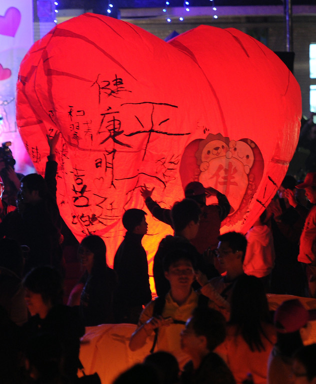 Description of . Local residents release a heart-shaped sky lantern in Pingshi, the New Taipei City, on the fifth day of the lunar new year on February 14, 2013.  At least 600 couples celebrated their Valentine's day via releasing sky lenterns on the lunar new year of snake.  AFP PHOTO / Sam  YEH/AFP/Getty Images
