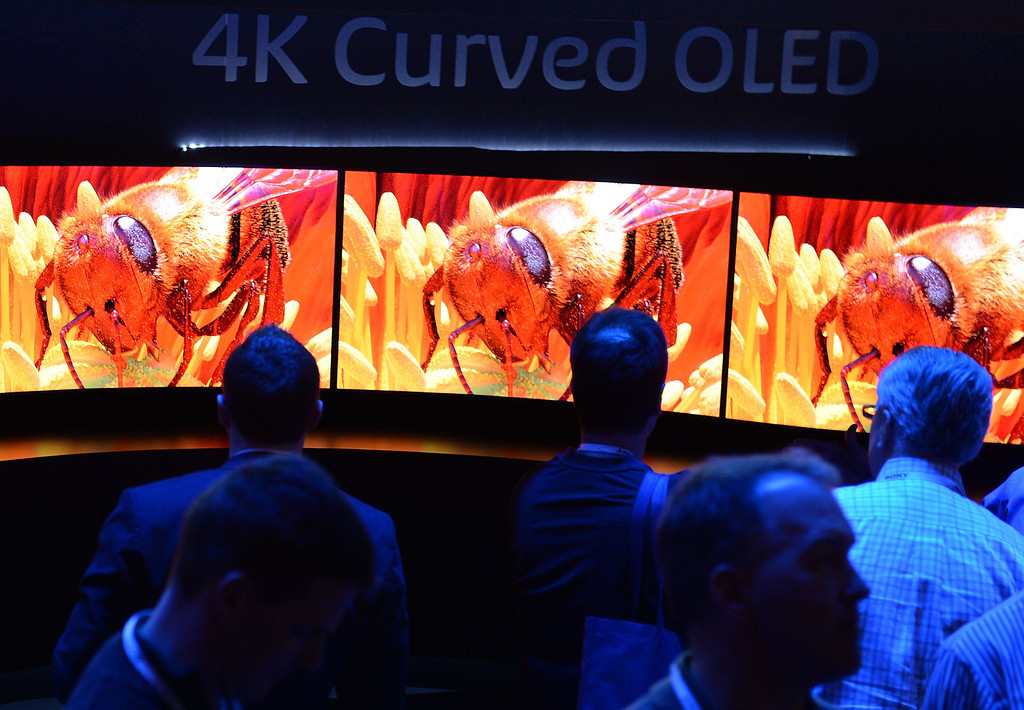 Description of . Attendees look at the 4K Curved OLED display at the Panasonic booth at the 2014 International CES in Las Vegas, Nevada, January 8, 2014.  The Consumer Electronics Show, one of the largest in the world, runs from Jan 7-10. AFP PHOTO / Robyn Beck/AFP/Getty Images