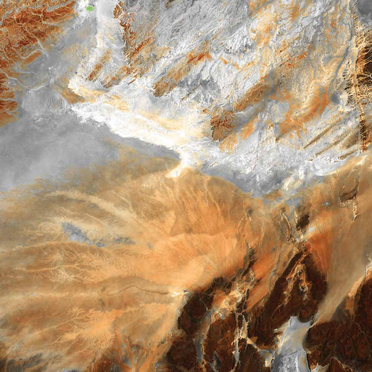 Description of . Algerian Desert, Algeria Lying amid the Great Eastern Erg, the Great Western Erg, and the Atlas Mountains in Northern Africa, the Sahara Desert in central Algeria is dotted by fragmented mountains (in brown, lower right) where barren, windswept ridges overlook arid plains. In this Landsat 5 image from 2009, a system of dry streambeds crisscrosses the rocky landscape awaiting the rare, intense rains that often cause flash floods.   NASA