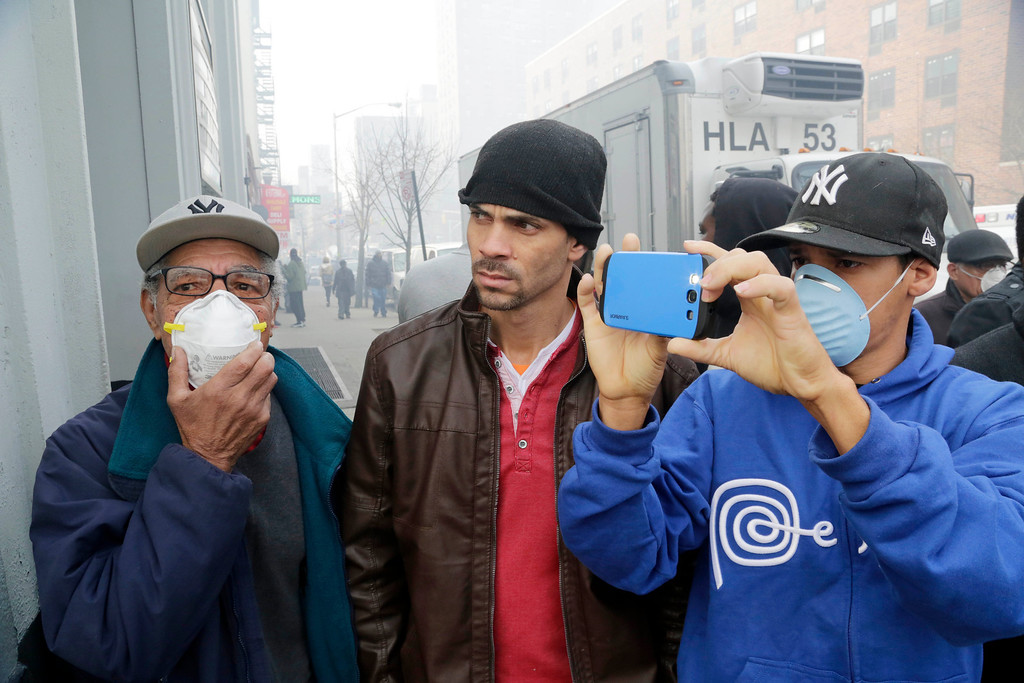 Description of . Passersby watch as rescue efforts continue after an explosion and building collapse in the East Harlem neighborhood of New York, Wednesday, March 12, 2014.  (AP Photo/Mark Lennihan)