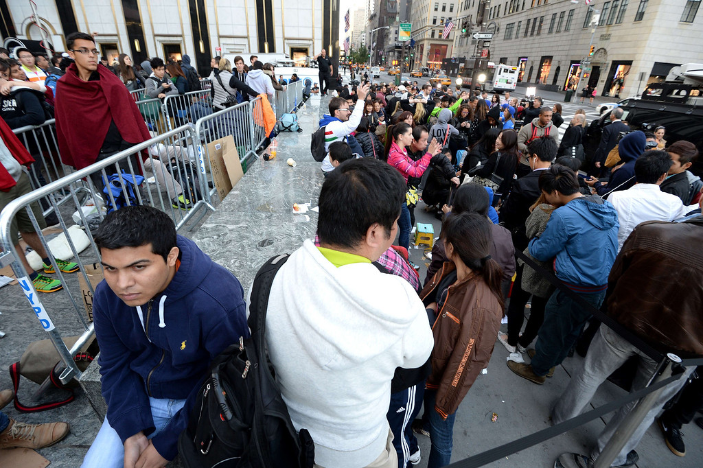 Description of . People waiting to buy the Apple iPhone 5 in line outside the Apple Store on Fifth Avenue September 20, 2013 in New York. Some people waited as long as fifteen days in line outside the store to be the first to buy the phone. AFP PHOTO/Stan HONDA/AFP/Getty Images