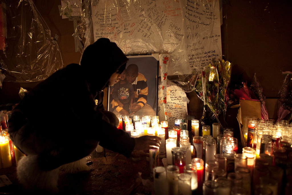 Description of . A mourner lights candles at a memorial for 16-year-old Kimani