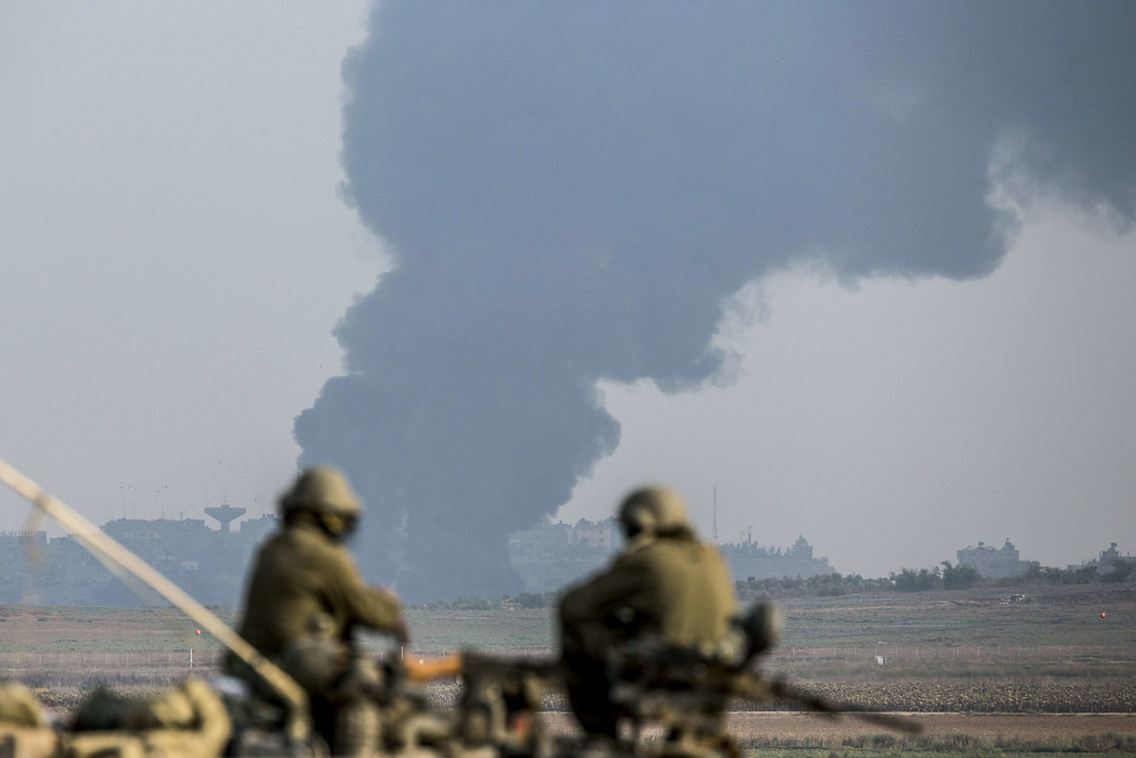 Description of . TOPSHOTS Israeli soldiers sitting on a tank hold their position on the Israeli side of the border with the Gaza Strip, on July 22 , 2014, as smoke billows from the coastal Palestinian enclave following an Israeli army ground operation to destroy tunnels reportedly used by Palestinian militants from the Gaza Strip to enter Israel. The UN chief and Washington's top diplomat are holding a flurry of meetings in Cairo to push for an end to two weeks of violence in Gaza that has killed sofar 585 Palestinians. AFP PHOTO / JACK GUEZ/AFP/Getty Images