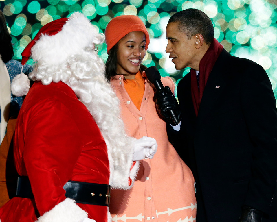 Description of . President Barack Obama, right, and daughter Malia Obama, sing as Santa Claus arrives during the 90th annual National Christmas Tree Lighting ceremony on the Ellipse south of the White House, Thursday, Dec. 6, 2012, in Washington. (AP Photo/Alex Brandon)