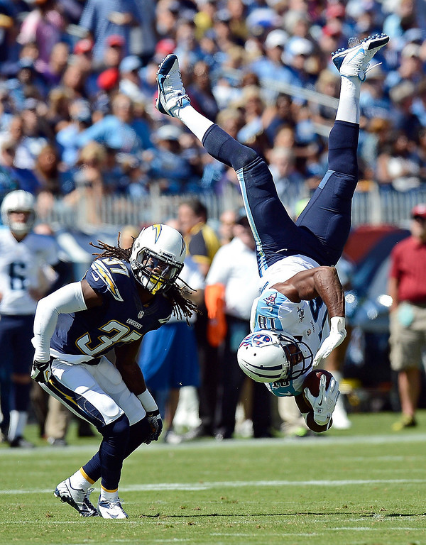 Description of . Tennessee Titans wide receiver Kenny Britt (18) flips upside down after making a catch as he is defended by San Diego Chargers defensive back Jahleel Addae (37) in the second quarter of an NFL football game on Sunday, Sept. 22, 2013, in Nashville, Tenn.  Britt was unable to hold onto the ball and the pass was incomplete. (AP Photo/Mark Zaleski)