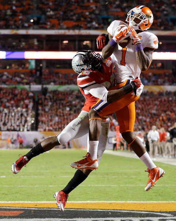 Description of . Clemson wide receiver Martavis Bryant (1) makes a catch for a touchdown as Ohio State cornerback Armani Reeves defends during the first half of the Orange Bowl NCAA college football game, Friday, Jan. 3, 2014, in Miami Gardens, Fla. (AP Photo/Wilfredo Lee)