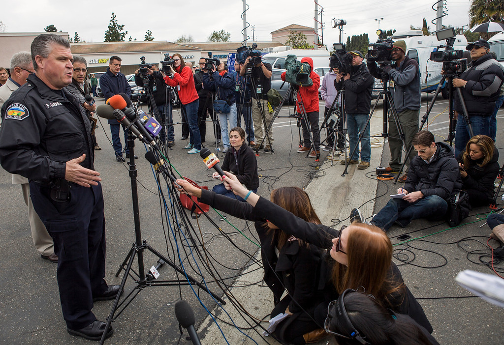 . Lt. Paul Garaven of the Tustin Police Department, left, takes question from the media regarding a shooting spree in Tustin, Calif., Tuesday, Feb. 19, 2013.  (AP Photo/Damian Dovarganes)