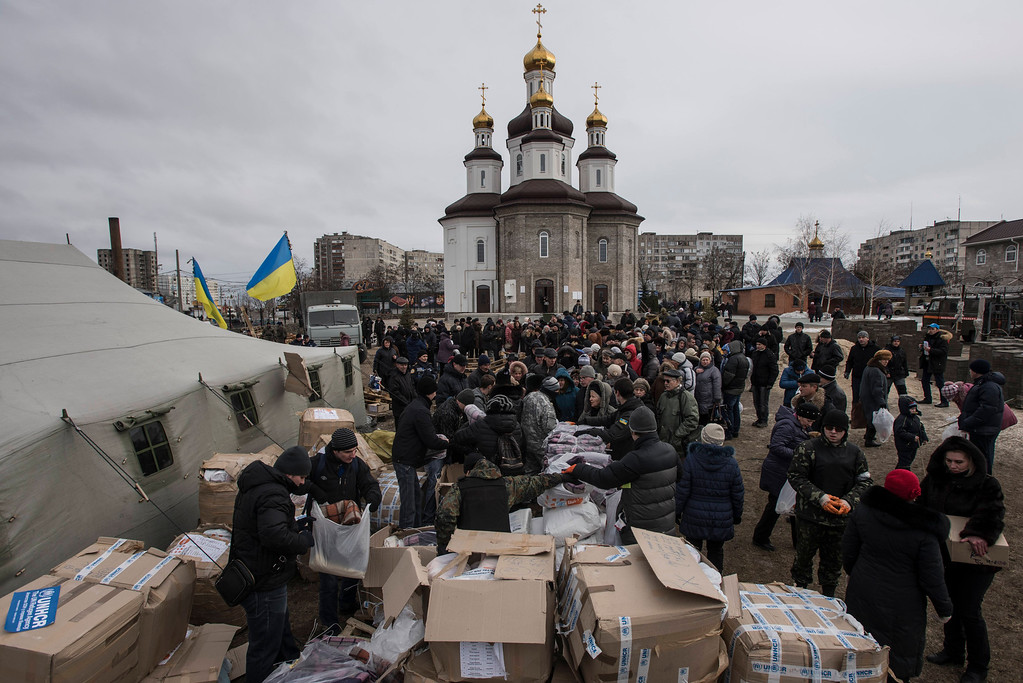 Description of . Volunteers distribute humanitarian aid after Saturday's attacks, in Mariupol, Ukraine, Sunday, Jan. 25, 2015. Indiscriminate rocket fire slammed into a market, schools, homes and shops Saturday in Ukraine's southeastern city of Mariupol, killing at least 30 people, authorities said. The Ukrainian president called the blitz a terrorist attack and NATO and the U.S. demanded that Russia stop supporting the rebels. (AP Photo/Evgeniy Maloletka)