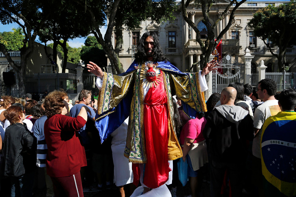 Description of . A man dressed as Jesus Christ poses for a photo as he waits with others for Pope Francis to give Angelus noon prayer at the Sao Joaquim Palace in Rio de Janeiro, Brazil, Friday, July 26, 2013. Pope Francis is on the fifth day of his trip to Brazil where he will attend the 2013 World Youth Day in Rio. (AP Photo/Jorge Saenz)