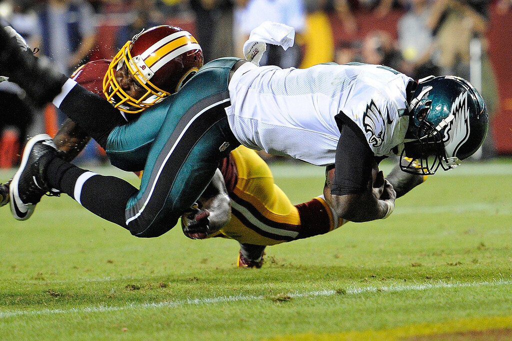 Description of . Philadelphia Eagles quarterback Michael Vick, right, scores a touchdown on the quarterback keeper under pressure from Washington Redskins strong safety Bacarri Rambo during the first half of an NFL football game in Landover, Md., Monday, Sept. 9, 2013. (AP Photo/Nick Wass)