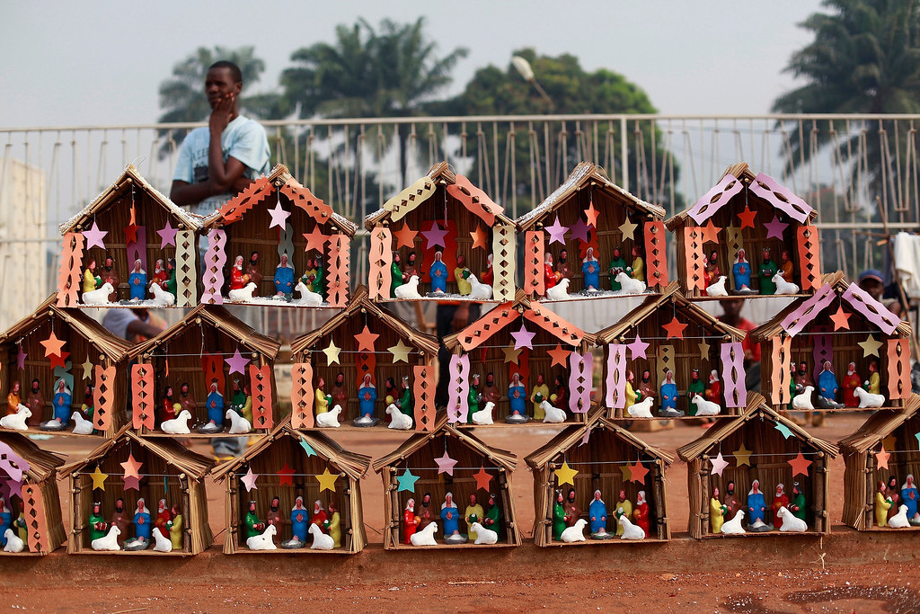 Description of . A man selling nativity scenes made from clay and reeds waits for clients in downtown Bangui, Central African Republic, Tuesday, Dec. 24, 2013. In the nation's capital riven by sectarian violence, Christmas shoppers were few this year. Those that did venture out found only a handful of vendors selling plastic toys and Christmas decorations. (AP Photo/Rebecca Blackwell)
