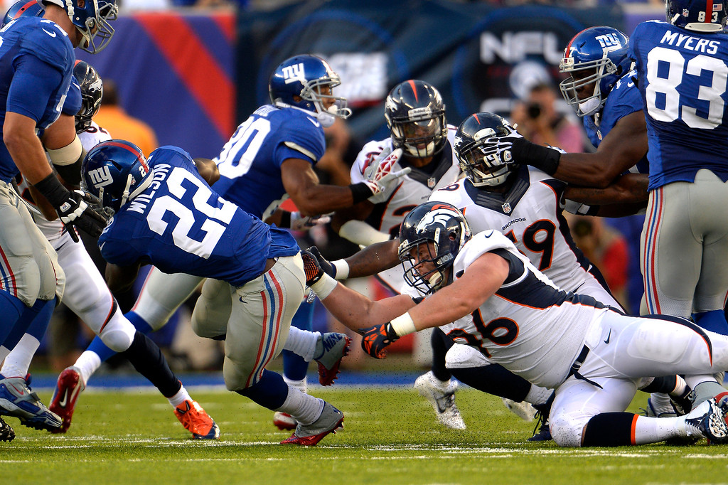 Description of . September 15: Defensive tackle Mitch Unrein (96) of the Denver Broncos fills the hole and sends running back David Wilson (22) of the New York Giants to the outside at METLIFE Stadium. September 15, 2013 East Rutherford, NJ. (Photo By Joe Amon/The Denver Post)