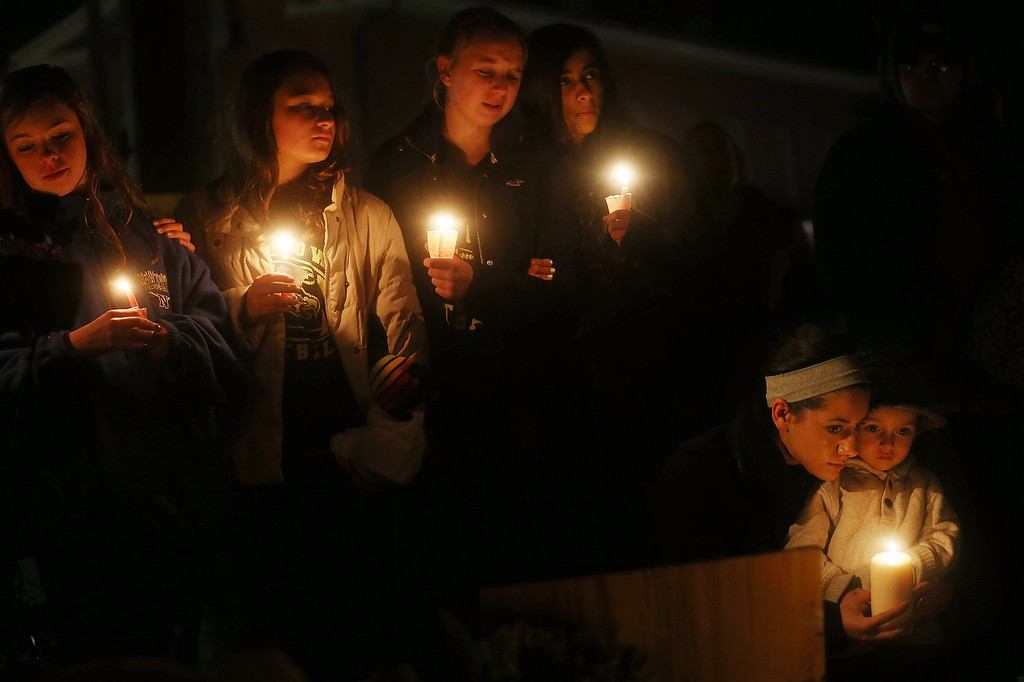 Description of . NEWTOWN, CT - DECEMBER 16: (L-R) Newtown residents Claire Swanson, Kate Suba, Jaden Albrecht, Simran Chand and New London, Connecticut residents Rachel Pullen and her son Landon DeCecco, hold candles at a memorial for victims on the first Sunday following the mass shooting at Sandy Hook Elementary School on December 16, 2012 in Newtown, Connecticut. U.S. President Barack Obama visited the grief stricken town today. (Photo by Mario Tama/Getty Images)
