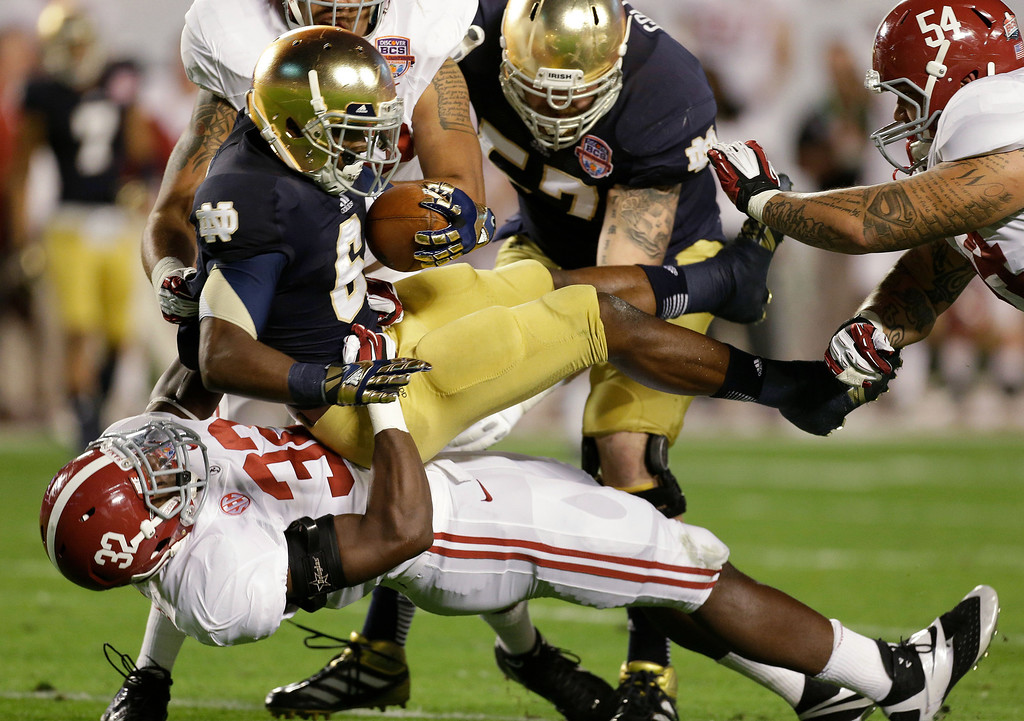 Description of . Alabama's C.J. Mosley (32) takes down Notre Dame's Theo Riddick (6) during the first half of the BCS National Championship college football game Monday, Jan. 7, 2013, in Miami. (AP Photo/Chris O'Meara)