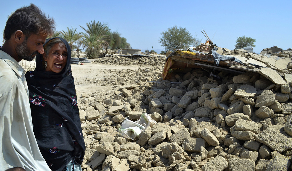 Description of . Pakistani villagers look for belongings amid the rubble of their destroyed homes following an earthquake in the remote district of Awaran, Baluchistan province, Pakistan, Wednesday, Sept. 25, 2013. (AP Photo/Arshad Butt)