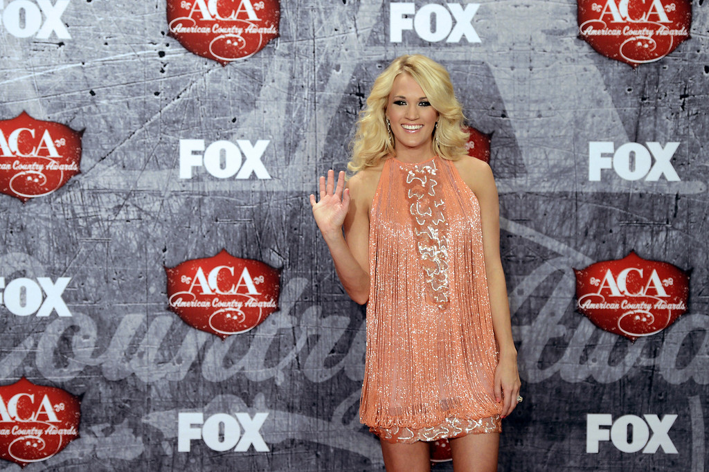 Description of . Singer Carrie Underwood poses in the press room with her awards for Female Artist of the Year and Single by a Vocal Collaboration backstage at the American Country Awards on Monday, Dec. 10, 2012, in Las Vegas. (Photo by Jeff Bottari/Invision/AP)