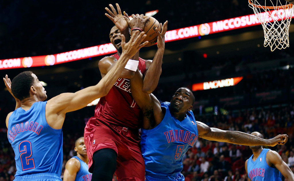 Description of . Oklahoma City Thunder'S Thabo Sefolosha (2) and Kendrick Perkins (5) defend Miami Heat's Chris Bosh (1) during the first half of an NBA basketball game, Tuesday, Dec. 25, 2012, in Miami. (AP Photo/J Pat Carter)
