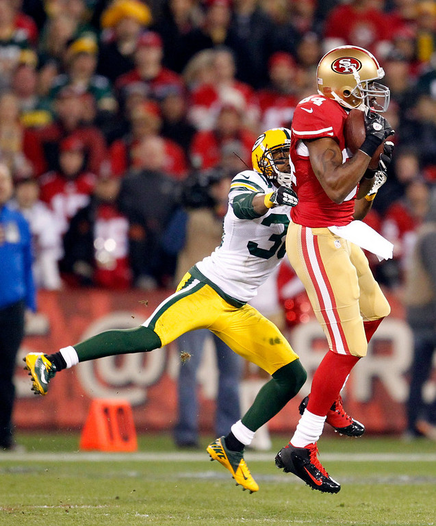 Description of . San Francisco 49ers wide receiver Randy Moss (84) catches a pass over Green Bay Packers cornerback Tramon Williams (38) during the first half of an NFC divisional playoff NFL football game in San Francisco, Saturday, Jan. 12, 2013. (AP Photo/Tony Avelar)