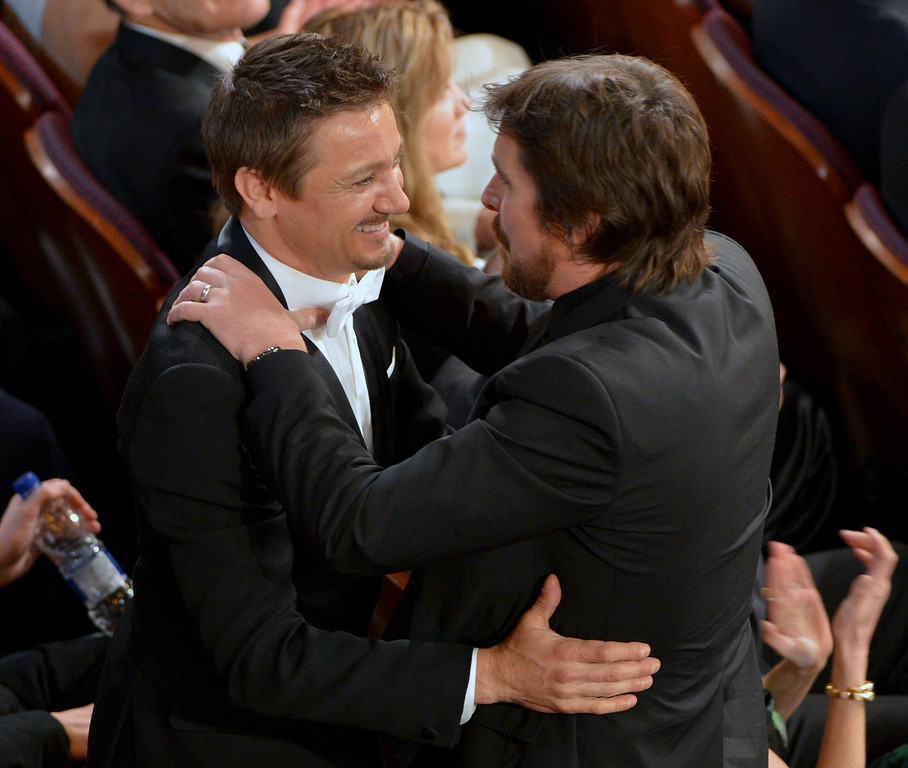 Description of . Jeremy Renner, left, and Christian Bale embrace in the audience at the Oscars at the Dolby Theatre on Sunday, March 2, 2014, in Los Angeles.  (Photo by John Shearer/Invision/AP)
